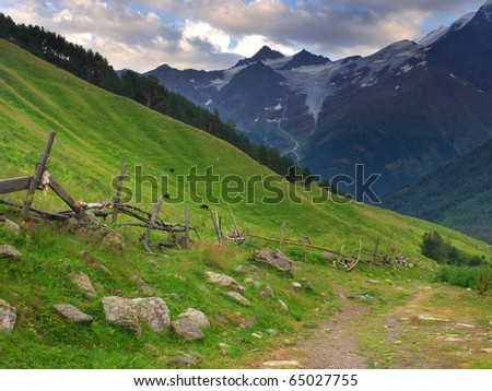 Road and fence on background of the high mountains. Natural composition - stock photo