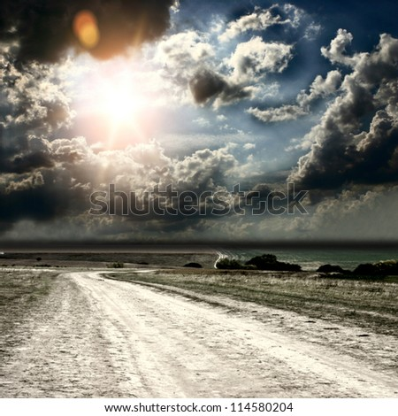 road and fields on the background of the beautiful sky - stock photo