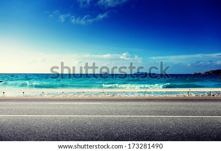 road and sea in sunset time - stock photo