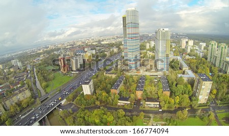 Road and skyscrapers in city at cloudy day. View from unmanned quadrocopter. - stock photo