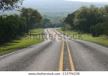 Road and trees in the Texas Hill Country - stock photo