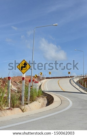Road and winding road sign