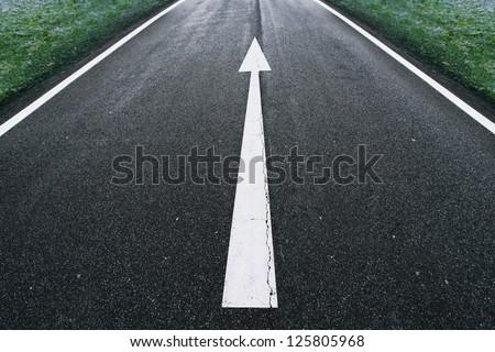 Road arrow direction sign on the asphalt ground. - stock photo