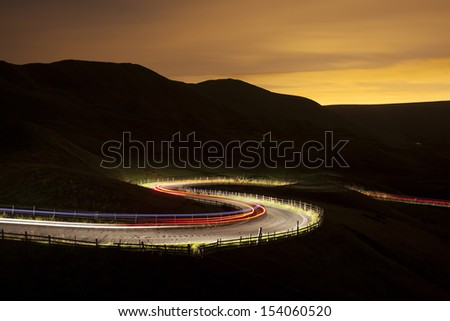 road at night with car light trail in rural England - stock photo