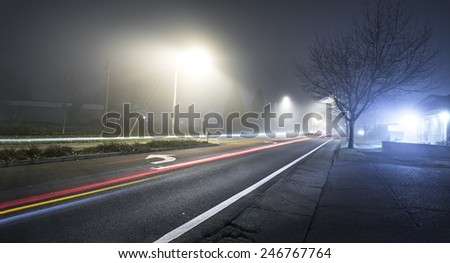 Road at night with fog and long exposure of car trail with sidewalk to the right - stock photo