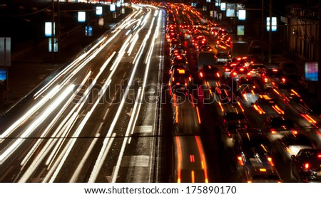 Road at night with traffic trails and blurred lights - stock photo