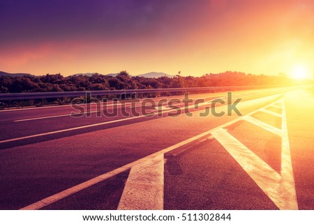 Road at sunset time. Remote hill on horizon