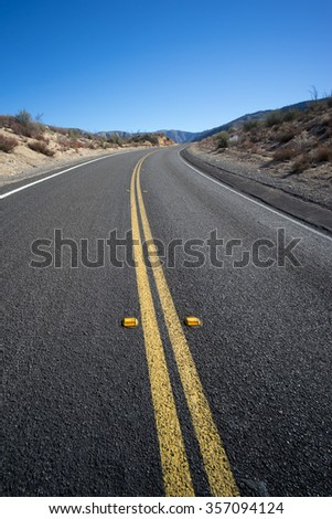 Road bends around curve in the desert wilderness of the American southwest. - stock photo