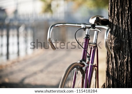Road bicycle on city street, cycling in summer nature, vintage old retro bike, cycling or commuting in city urban environment, ecological transportation concept - stock photo
