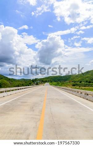 road bridge highway along mountain and blue sky - stock photo