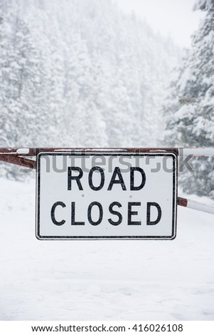 Road closed sign blocking dangerous snow ice weather covered road with covered trees and icy surface - stock photo