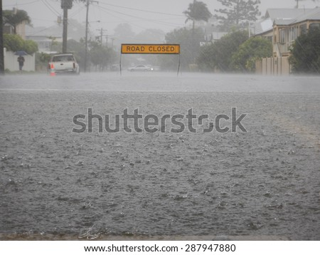 Road Closed sign on a flooded street in heavy rain. In the forground is a huge floodwater puddle with heavy raindrops. - stock photo
