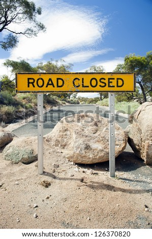Road closed sign with large boulders on the road