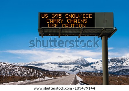 Road Conditions Sign:  A lighted message warns travelers to prepare for hazardous driving conditions on a Sierra Nevada mountain road.  - stock photo