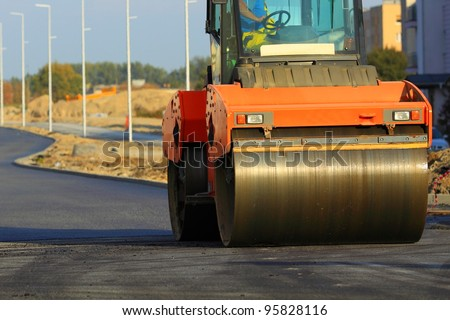 Road construction. Large rolling machinery paving a road