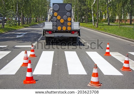 Road construction site with signs and orange road hazard cone - stock photo