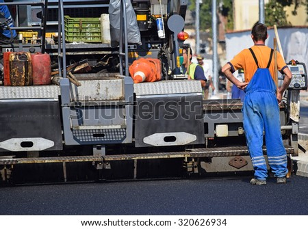 Road construction with an asphalt paving vehicle in the city - stock photo
