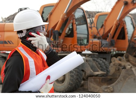 road construction worker holding blueprints and talking on the phone - stock photo