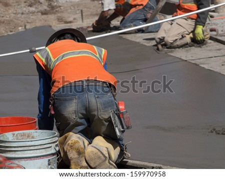 Road construction worker on new concrete road in downtown Denver, Colorado. - stock photo