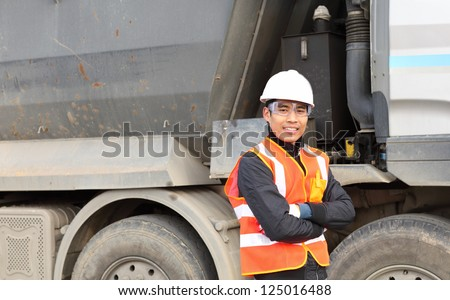 road construction worker standing beside the truck on location site
