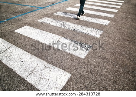Road crossing with pedestrian feet. Man walking and crossing the street. - stock photo