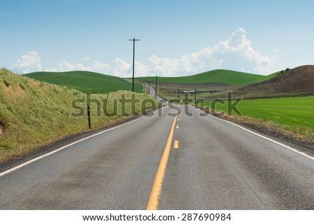 Road curving among rolling hills, Colfax, Washington - stock photo