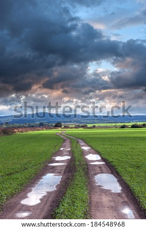 road, field and cloudy sky