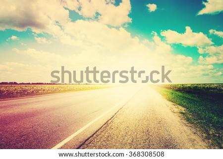 Road Field Landscape Blue Sky Sun Light on Horizon. Russian Route. Car Travel Scenic. Adventures Travel Concept - stock photo
