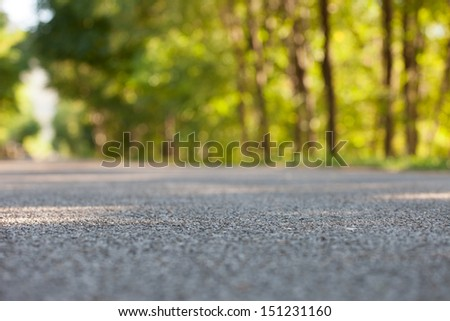 Road from the ground level - shallow depth of field and trees bokeh. - stock photo