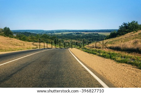 road going to distance against hilly landscape - stock photo