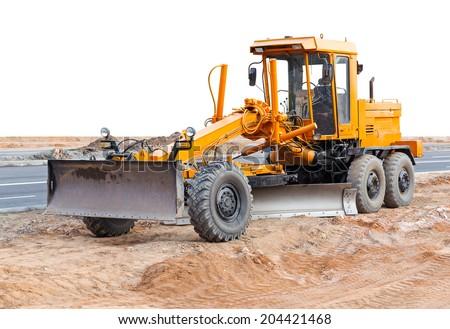 Road grader - heavy earth moving road construction equipment - stock photo