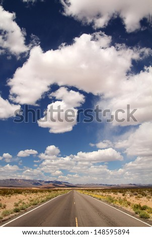 Road in a desert with beautiful blue sky full of clouds - stock photo