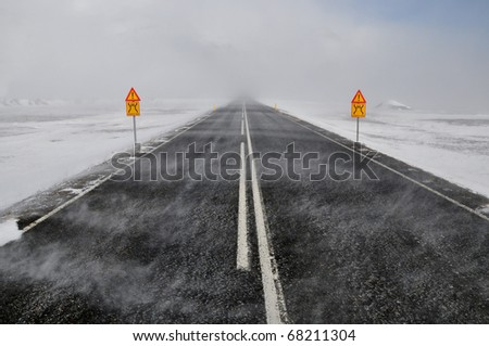 Road in a snow blizzard and two attention sing, Iceland - stock photo