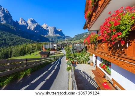 Road in alpine village with red flowers on house balcony, Colfosco, Dolomites Mountains, Italy