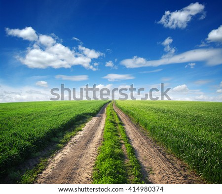 road in field and blue sky with clouds - stock photo