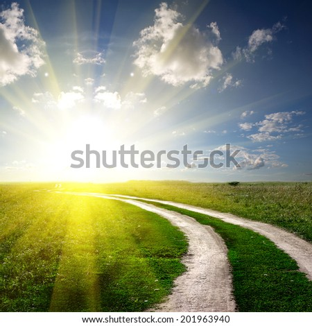 Road in field with clouds - stock photo