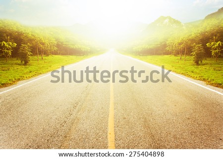 Road in forest against mountain and sky background with light bursts. - stock photo