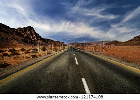 Road in jordanian desert with dramatic sky - stock photo