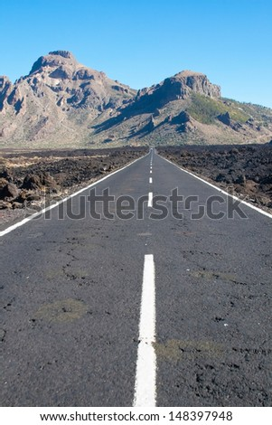 Road in lava fields near to Teide peak on Tenerife. Teide National Park. Canary islands. Spain - stock photo