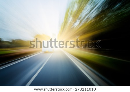 Road in motion blur�¯�¼? through the forest in sunset.