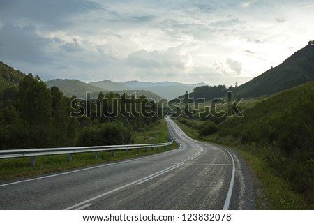 road in mountain under sky - stock photo