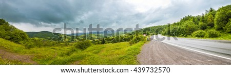 Road in mountains with dramatic sky and heavy clouds panorama