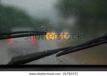 Road in rain through wind-screen of moving car - stock photo