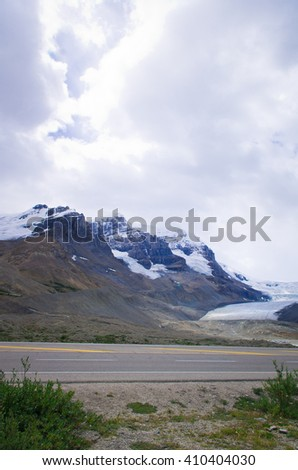 road in the Canadian Rockies, with snow mountains, blue key and cloud in the background - stock photo