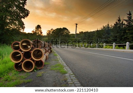 Road in the country, orange sunset sky and stack of pipes. - stock photo
