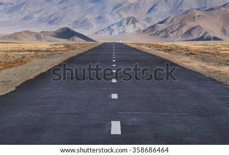 road in the middle of the steppe of Mongolia - stock photo