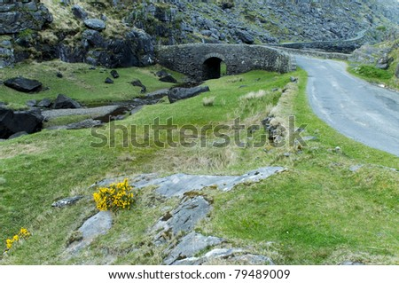 Road in the valley on the narrow part of Gap of Dunloe, Ireland - stock photo