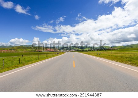road in tibetan meadow and skyline