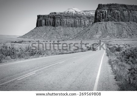 Road in United States - rural road in Utah leading to Canyonlands. Black and white tone - retro monochrome color style. - stock photo