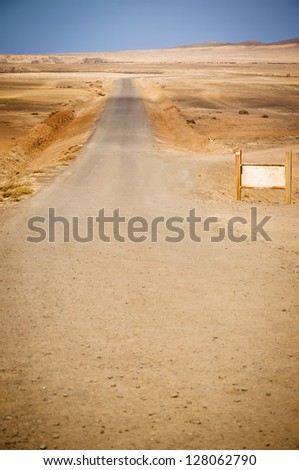 Road in volcanic landscape of Fuerteventura. Blank billboard - ready copy space. - stock photo